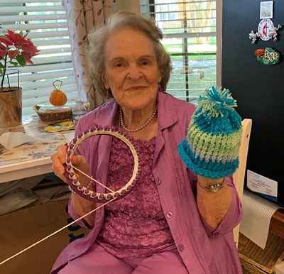 A woman smiling and holding up a hat that she created on a loom.