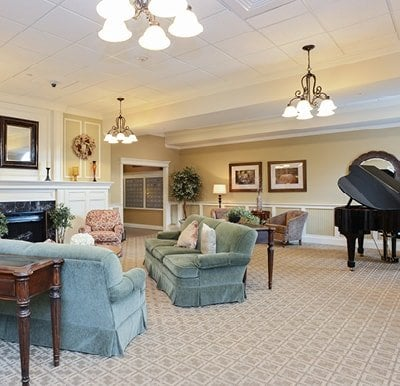 Comfortable lounge area with sofas and armchairs facing a fireplace, with a grand piano to the right in Springfield, Massachusetts.