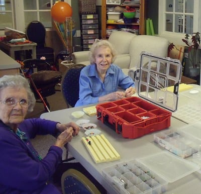 Residents participating in a jewelry making craft session.