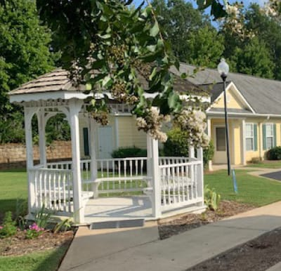A white gazebo with walking path and beautiful landscaping.