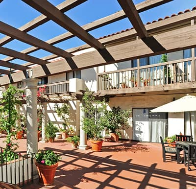 Beautiful terrace with pergola covering, outdoor seating and potted plants.