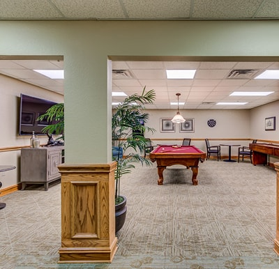 Senior living activity center in Hot Springs, Arkansas with billiards table and large screen flat TV.