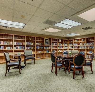 An overstocked library with games, tables and chairs in a senior living facility in Hot Springs, Arkansas.