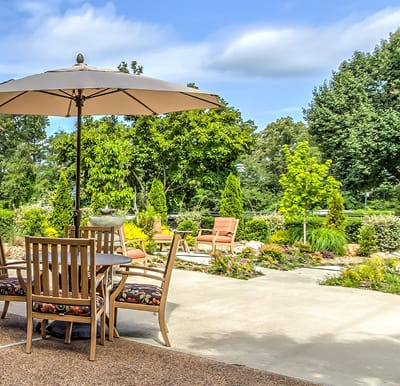 A landscaped courtyard at a senior living community with table and chairs.
