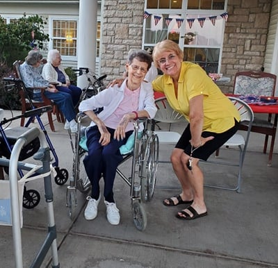 Residents and team members smiling and enjoying time on the patio on a nice day.