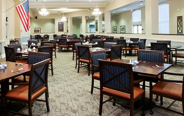 Bright, spacious dining room with many tables for 4 and an American flag in Richardson, Texas.
