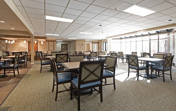 Large senior living facility dining room with many tables and large windows in Omaha, Nebraska.
