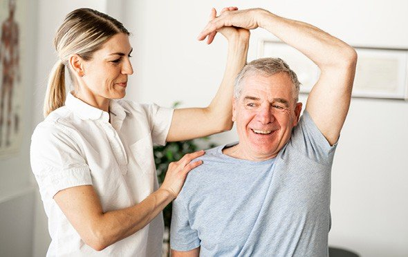 A physical therapist helping a senior stretch his tricep.