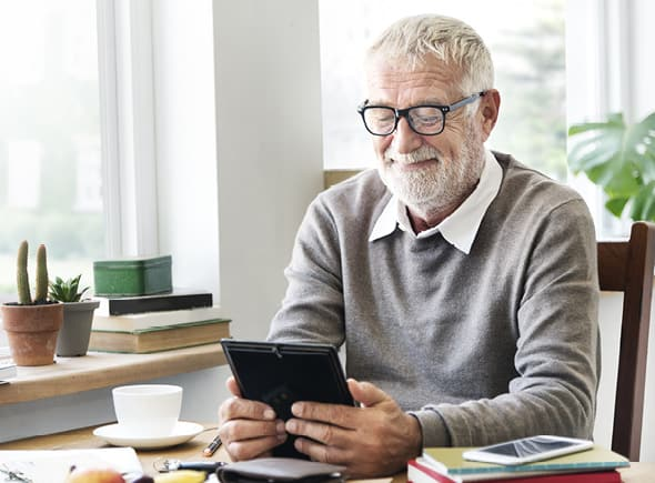 Man smiling and looking at a tablet.