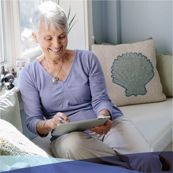 Woman sitting on the couch and looking at a tablet.