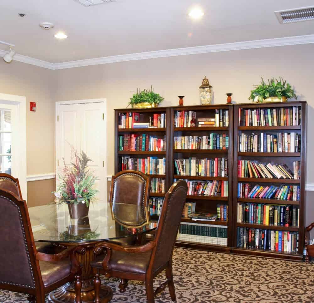 Library inside a senior living community in Stephenville, Texas with a table and chairs and shelves of books.
