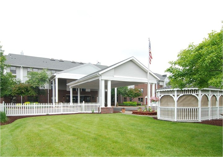 The entrance to a beautiful senior living community with well-manicured landscaping and a screened-in gazebo.