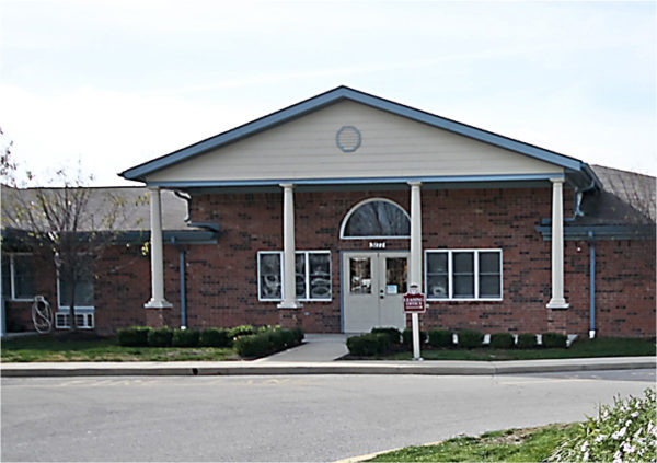 The entrance to a senior living community in Greenwood, Indiana with brick facade and white columns.