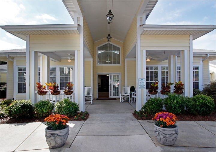 Front entrance of a senior living facility in Anderson, South Carolina with colorful flowers lining walking and white rocking chairs at entrance.