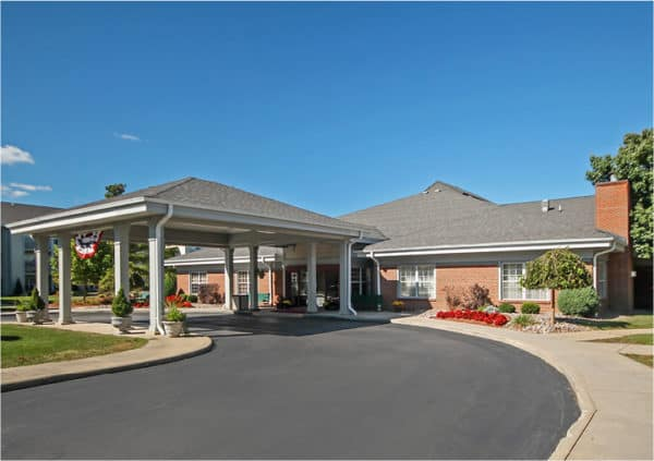 Front entrance of a senior living facility in Williamsville, New York with covered circular drive and lush landscaping.