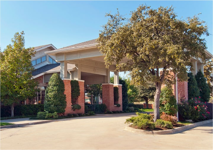 The outside of an independent living community in Irving, Texas with mature trees and lush grounds.