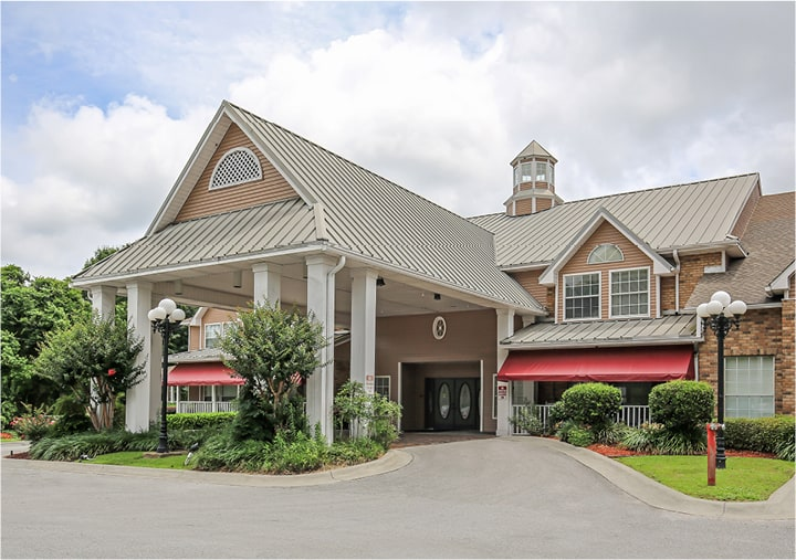 Front entrance of a coastal senior living facility in Pensacola, Florida with a covered driveway.