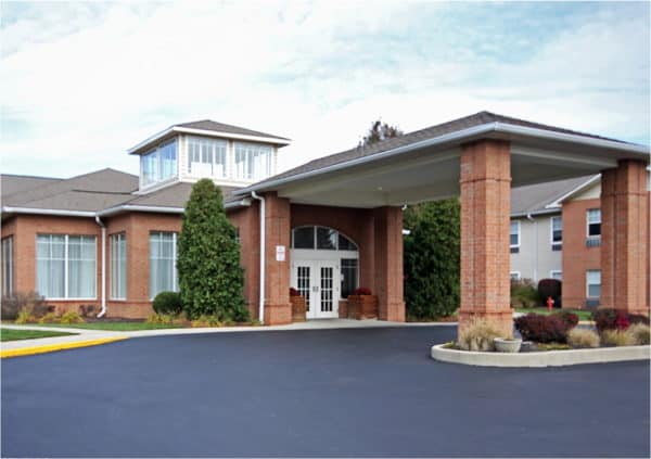 Senior living community building with brick, a grand portico with columns and balconies in Fairfield, Ohio.