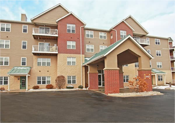 Senior living community entrance in Fitchburg, Wisconsin, with covered entryway and balconies.