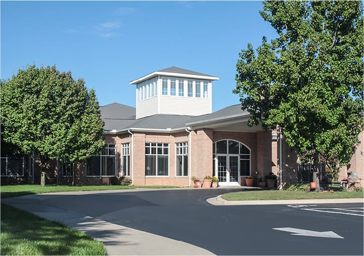 The exterior of a senior living community with a portico entrance, bench seating and landscaping in Springfield, Missouri.