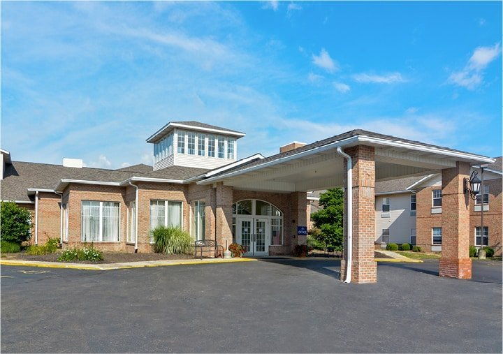 Front entrance of a senior living facility with portico entrance, bench seating and landscaping in Mansfield, Ohio.