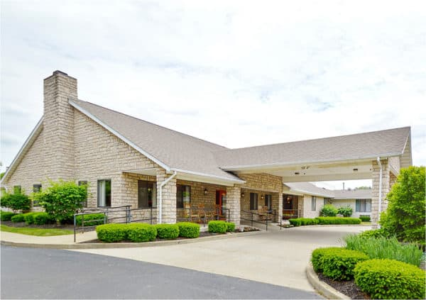 The entrance to a senior living community in Columbus, Ohio with brick facade and white columns.