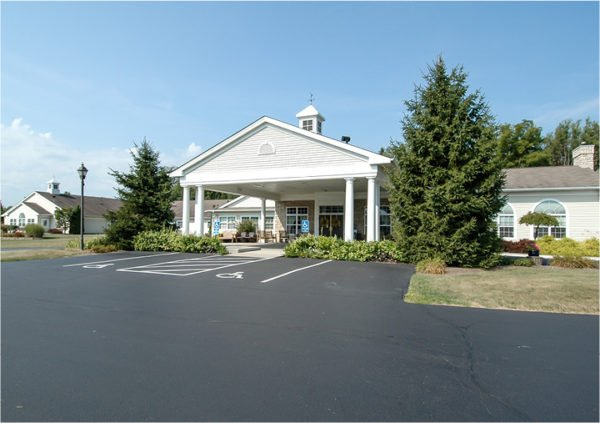 Front entrance of a senior living facility in Columbiana, Ohio with lush landscaping and covered entrance.