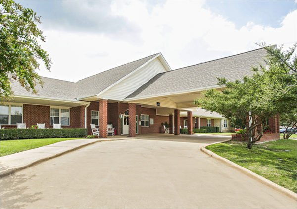Front entrance of a senior living facility in Keller, Texas with covered walkway and white rocking chairs.