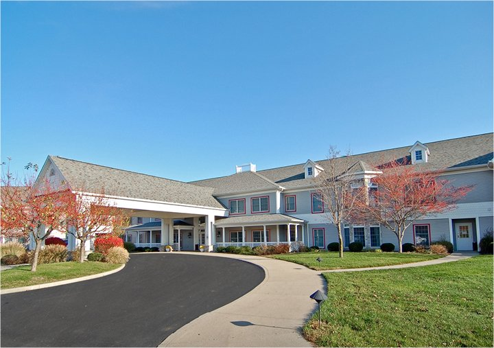 Front entrance of a senior living facility in Rochester, Indiana with circular driveway and covered entrance..