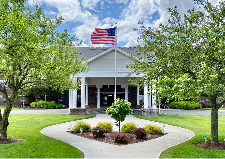 Front entrance of senior living building with spacious lawn, gazebo, portico and an American flag.