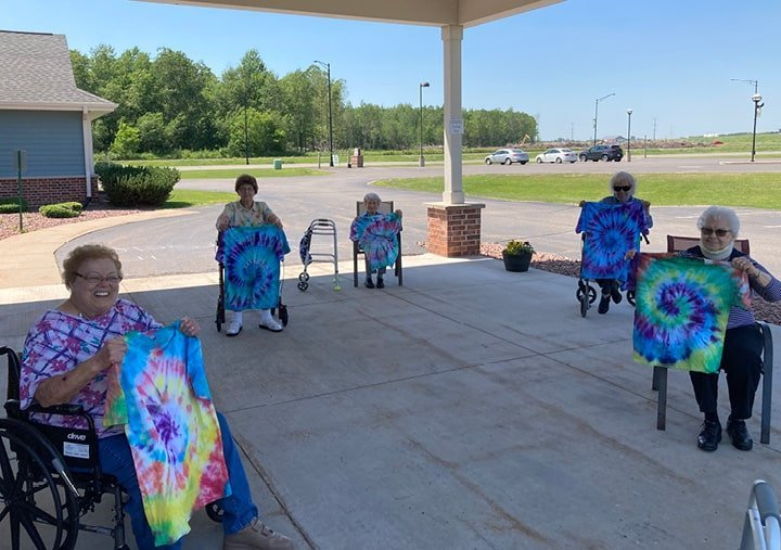 Seniors holding up tie dye t-shirts they made at their senior living community in Colby, Wisconsin.