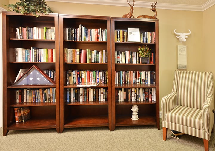 A library with comfortable armchair and deer statues on top of stocked bookshelves in Columbus, Ohio.