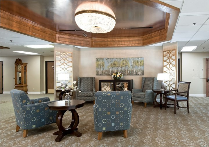 Senior living lounge area with comfortable seating under a beautiful chandelier in Omaha, Nebraska.