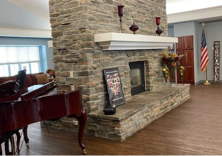 A double-sided, stone fireplace with a grand piano next to it in Elkhorn, Nebraska.