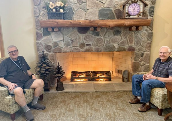 Senior men smiling and chatting in front of a fireplace in Maple Grove, Minnesota.