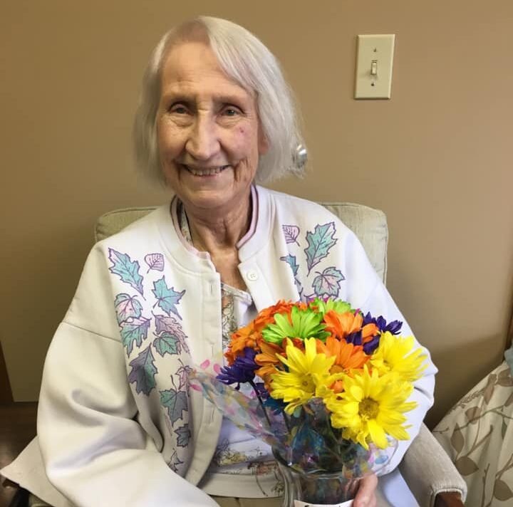 Senior woman smiles with some flowers at a senior living community in West Bend, Wisconsin.