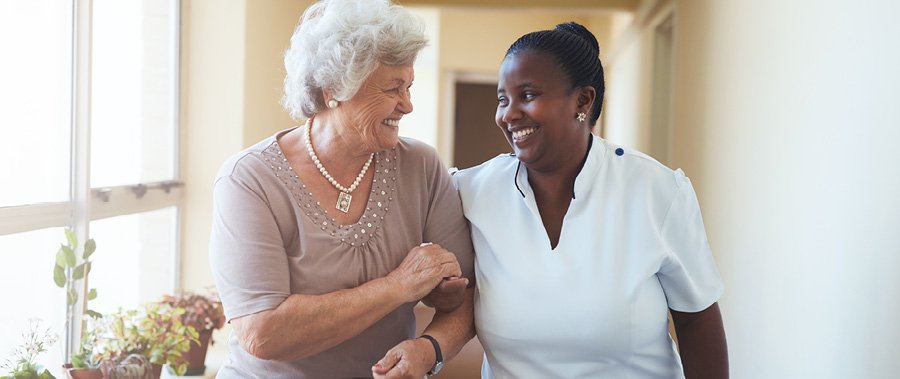 Senior woman being led down the hall by a smiling caregiver.