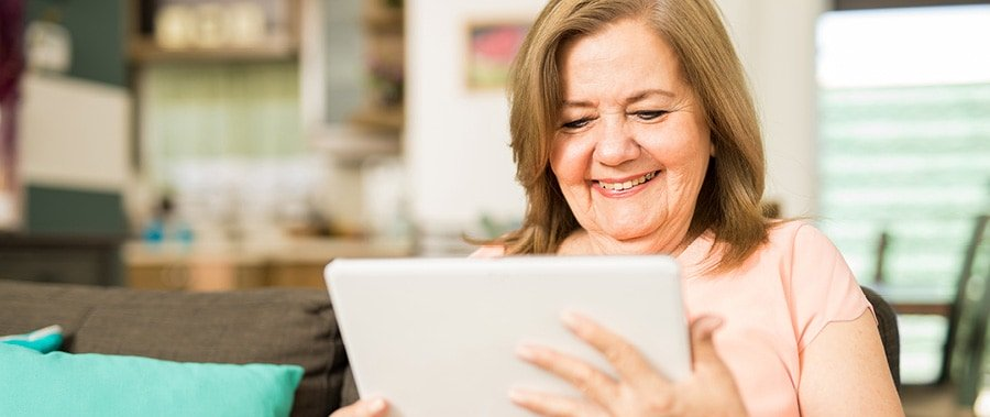 A smiling woman reading a blog on her tablet.