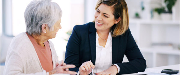 A financial planner smiling and helping a senior woman.