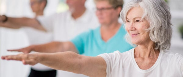 Senior woman holding a pose during a yoga class.