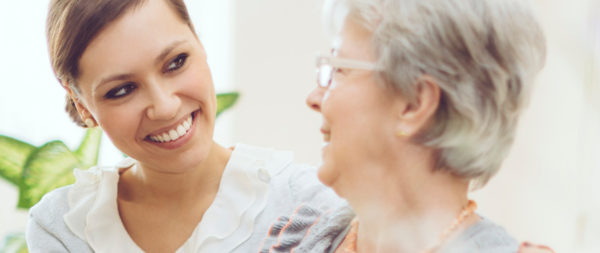 A smiling caregiver with her arm around a resident.