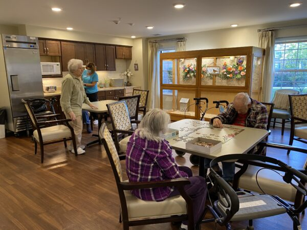 Two seniors do a puzzle together in a dining space at a senior living community in Fort Wayne, Indiana.