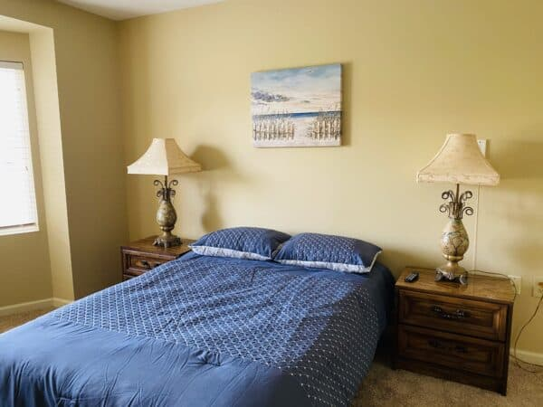 Senior apartment bedroom with queen bed and two side tables with lamps in Cincinnati, Ohio.
