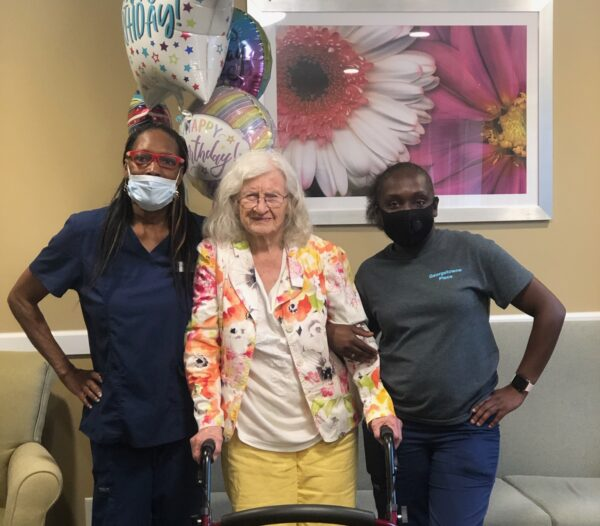 Senior woman smiles next to two caregivers during her birthday at a senior living community in Fort Wayne, Indiana.