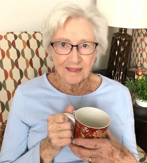 senior woman smiles with a mug at the Waterford at ironbridge senior living community in Springfield, Missouri