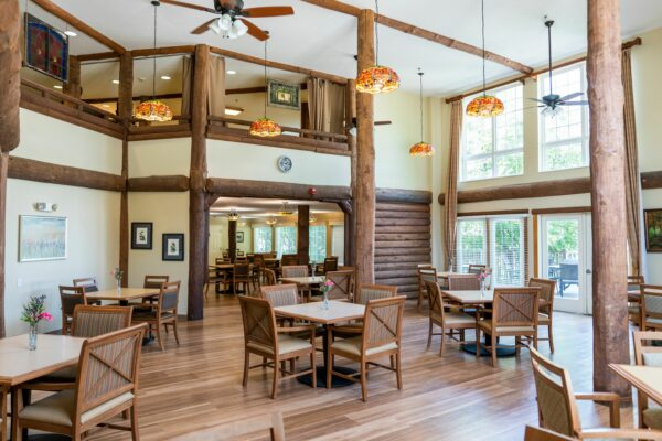 Rose Arbor and Wildflower Lodge dining room with soaring ceiling and wood exposed beams and columns at a senior living facility in Maple Grove, Minnesota.