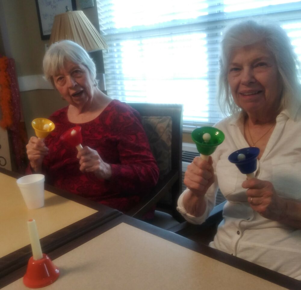 Two senior women participate in the bell choir at a senior living community in Indianapolis, Indiana.