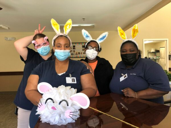 Four women employees pose together during Easter at a senior living community in Anderson, South Carolina.