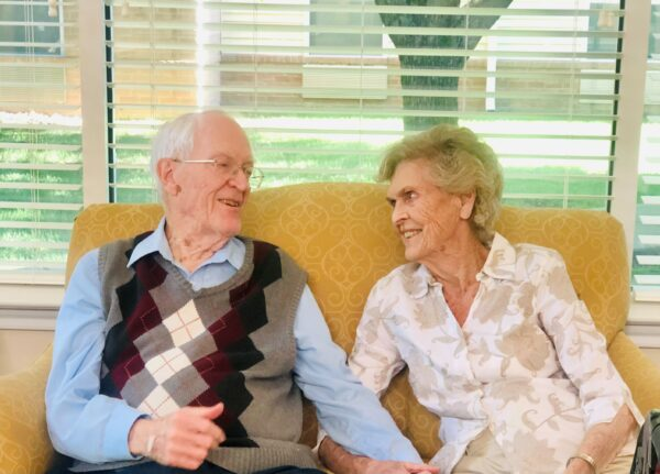 Senior man and woman smile at each other on the couch at a senior living community in Springfield, Missouri.
