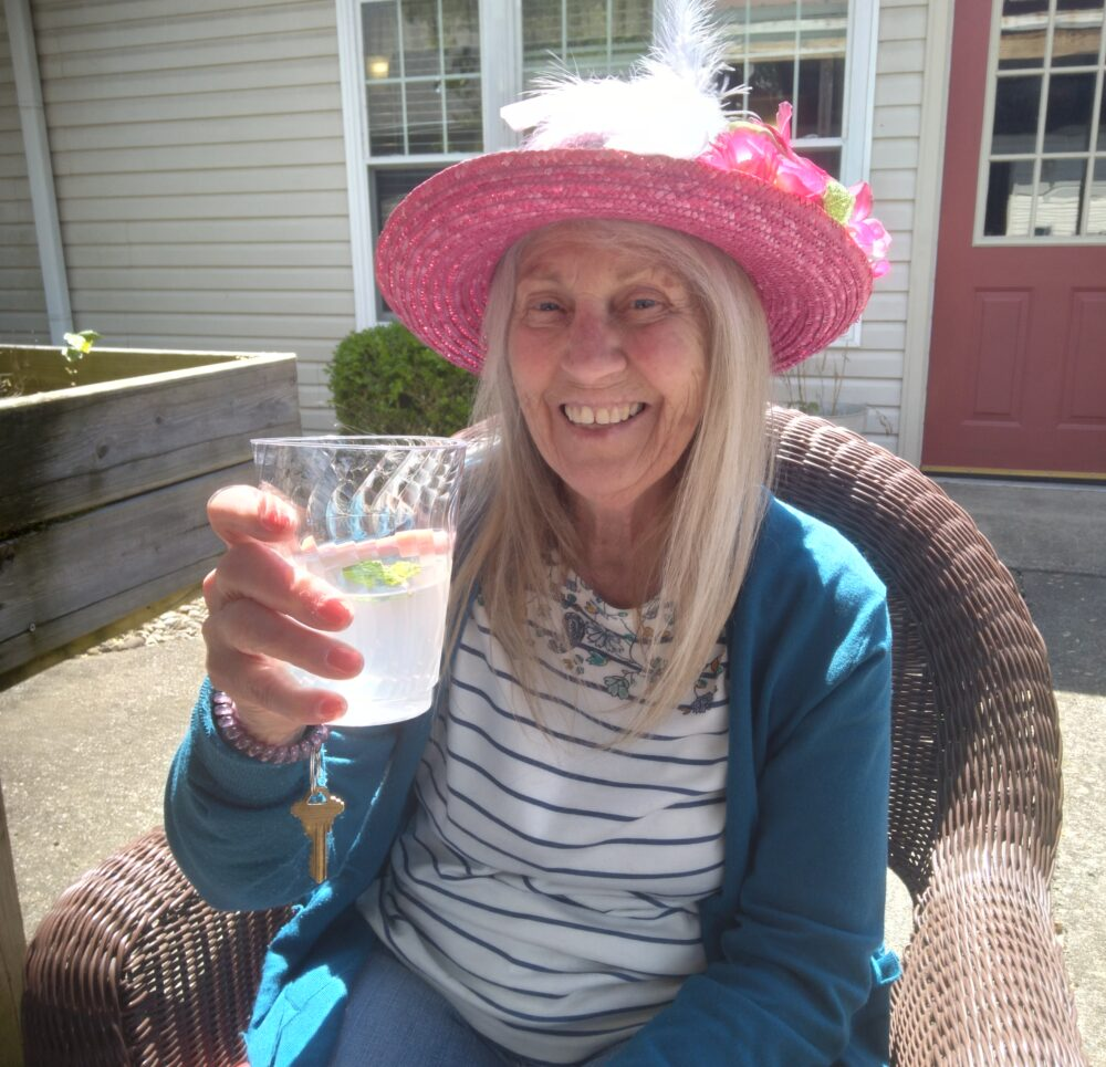 Senior woman celebrates the Kentucky Derby with a festive drink at a senior living community in Jeffersonville, Indiana.